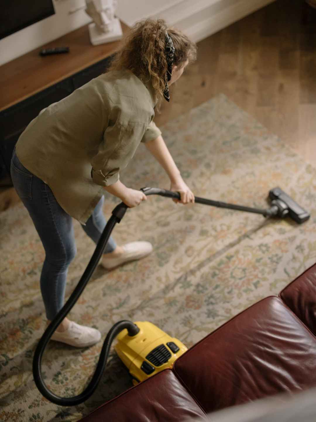 woman spring cleaning and vacuuming her carpet