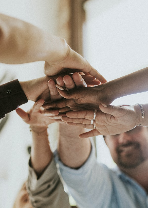 Employees putting hands in to show teamwork