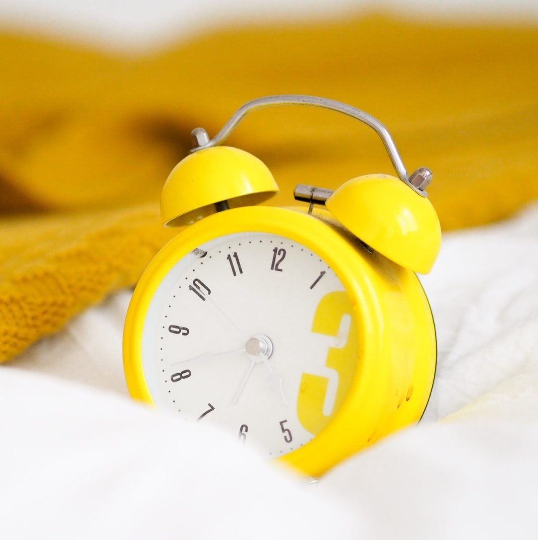 Old Fashioned Yellow Alarm Clock on a bed