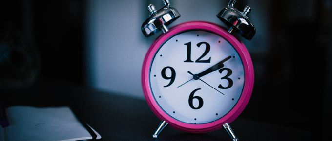 A small pink analog alarm clock