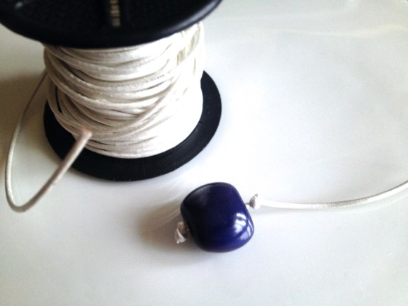 Insert white leather cord through bead and tie a knot on each end.