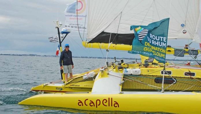 Do desátého ročníku Route du Rhum vyrazila i dvojice trimaranů, které byly sesterskými loděmi Olympus Photo, na němž Mike Birch porazil v prvním ročníku Kriter V. Jedním z nich byl žlutý Acapella.