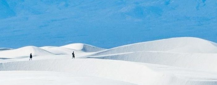 Three people walking on white snow with blue mountains in the background