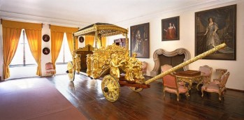 Anteroom containing golden carriage, chairs, and paintings