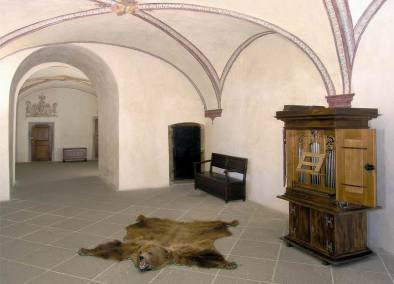 Arched ceiling and tiled floor, with organ and bear-skin rug