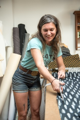 Anna Toth at work in her River Arts District studio cutting patterns for her her designs sold as Bow + Arrow Apparel.