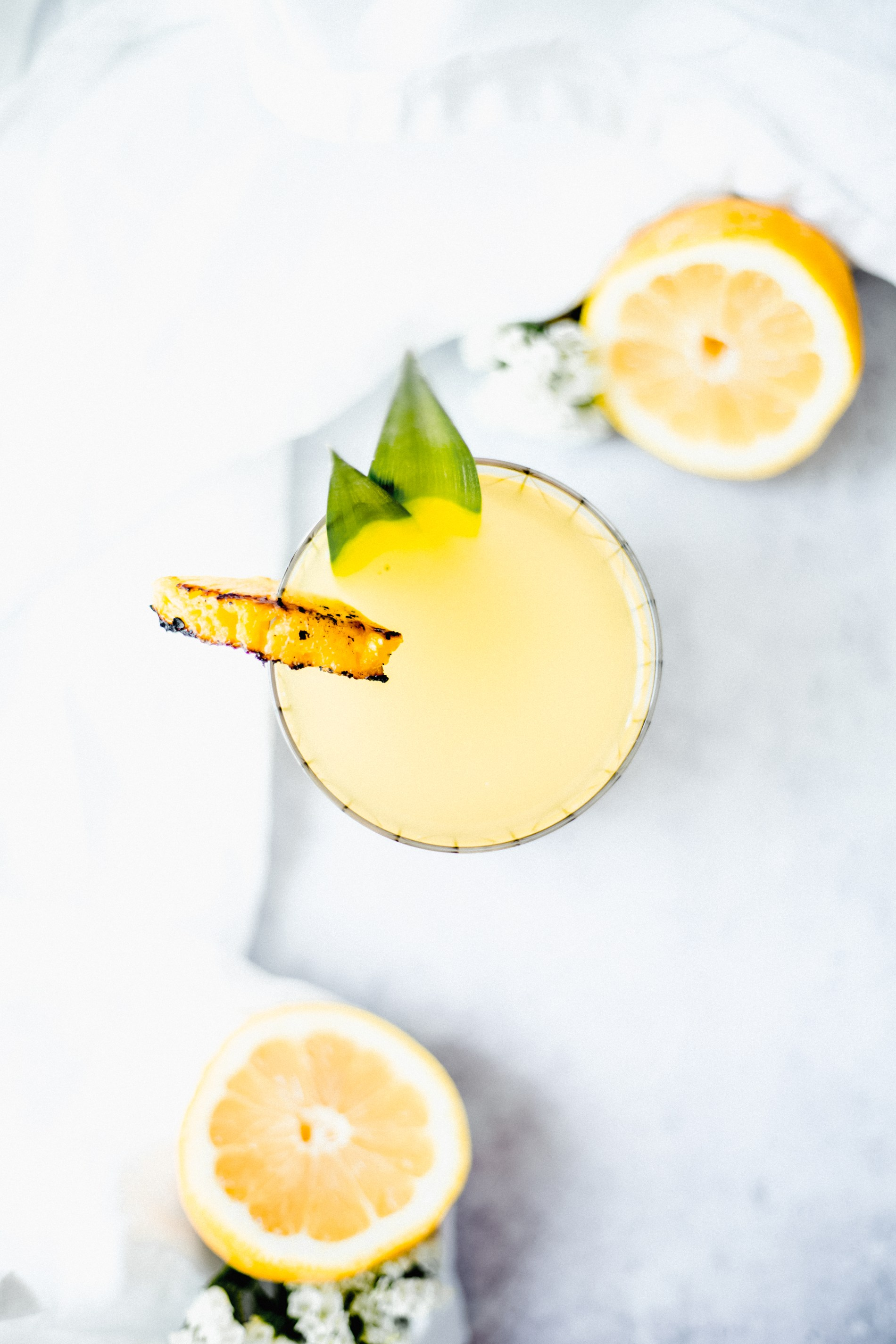 The cocktail that will be on repeat all summer long- Spiked Grilled Pineapple Lemonade! sweetened with Maple Syrup and a splash of Malibu Rum. #summercocktails #cocktailrecipes #pineapplecocktails #lemonade