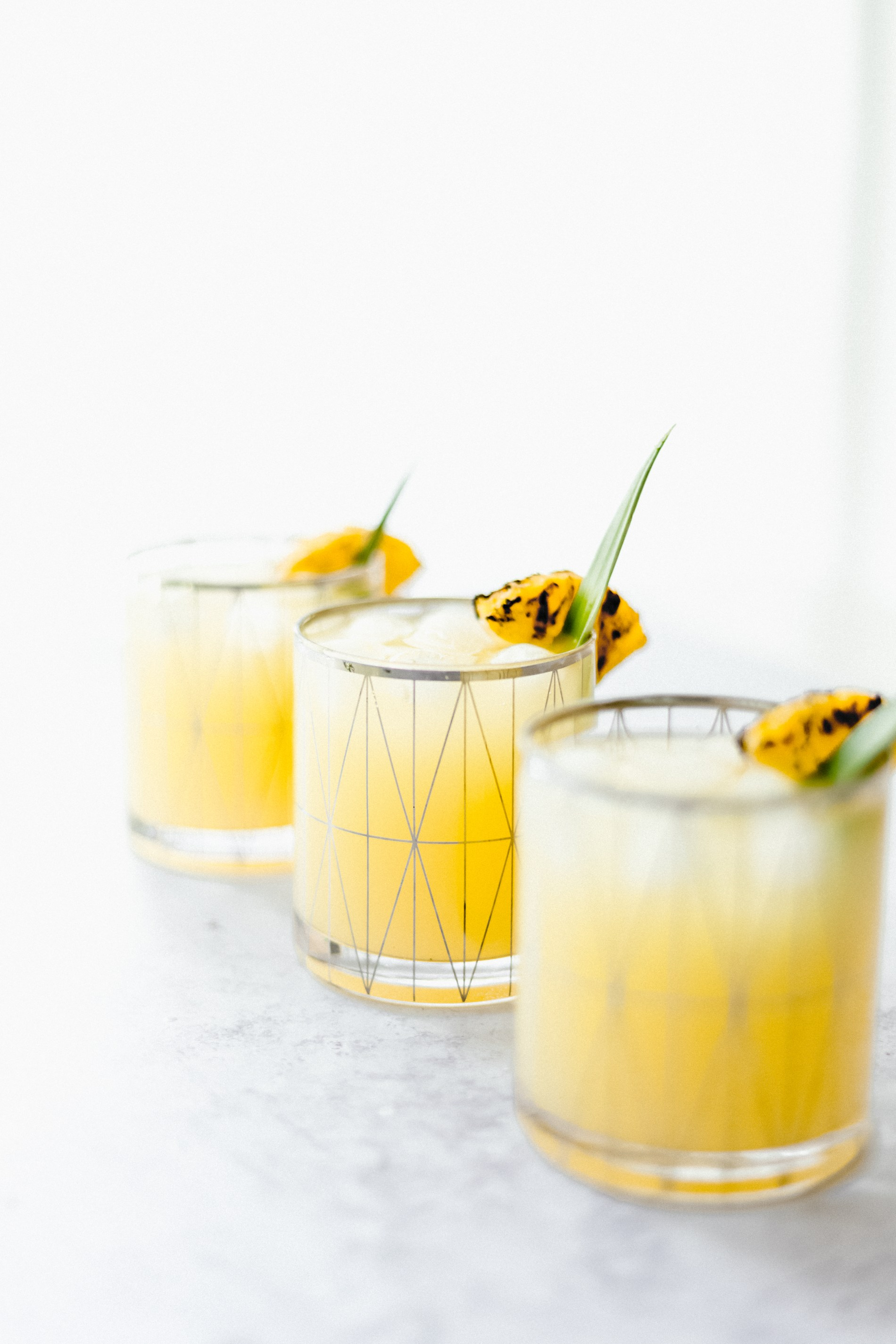 The cocktail that will be on repeat all summer long- Spiked Grilled Pineapple Lemonade! sweetened with Maple Syrup and a splash of Malibu Rum. #summercocktails #cocktailrecipes #pineapplecocktails #lemonade #drinkphotography
