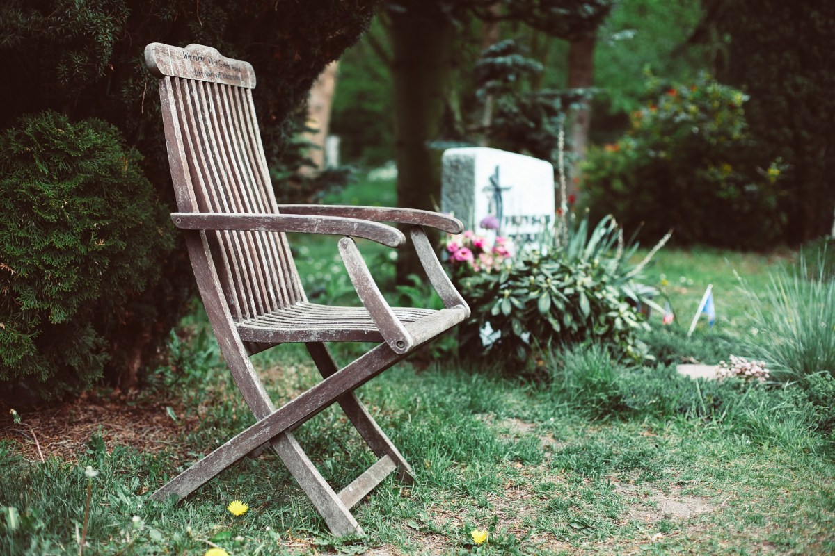 An image of a cemetery. In the foreground is an empty weathered wooden chair. Behind the chair is a headstone with a flowering plant in front of it. The grass is sparse.