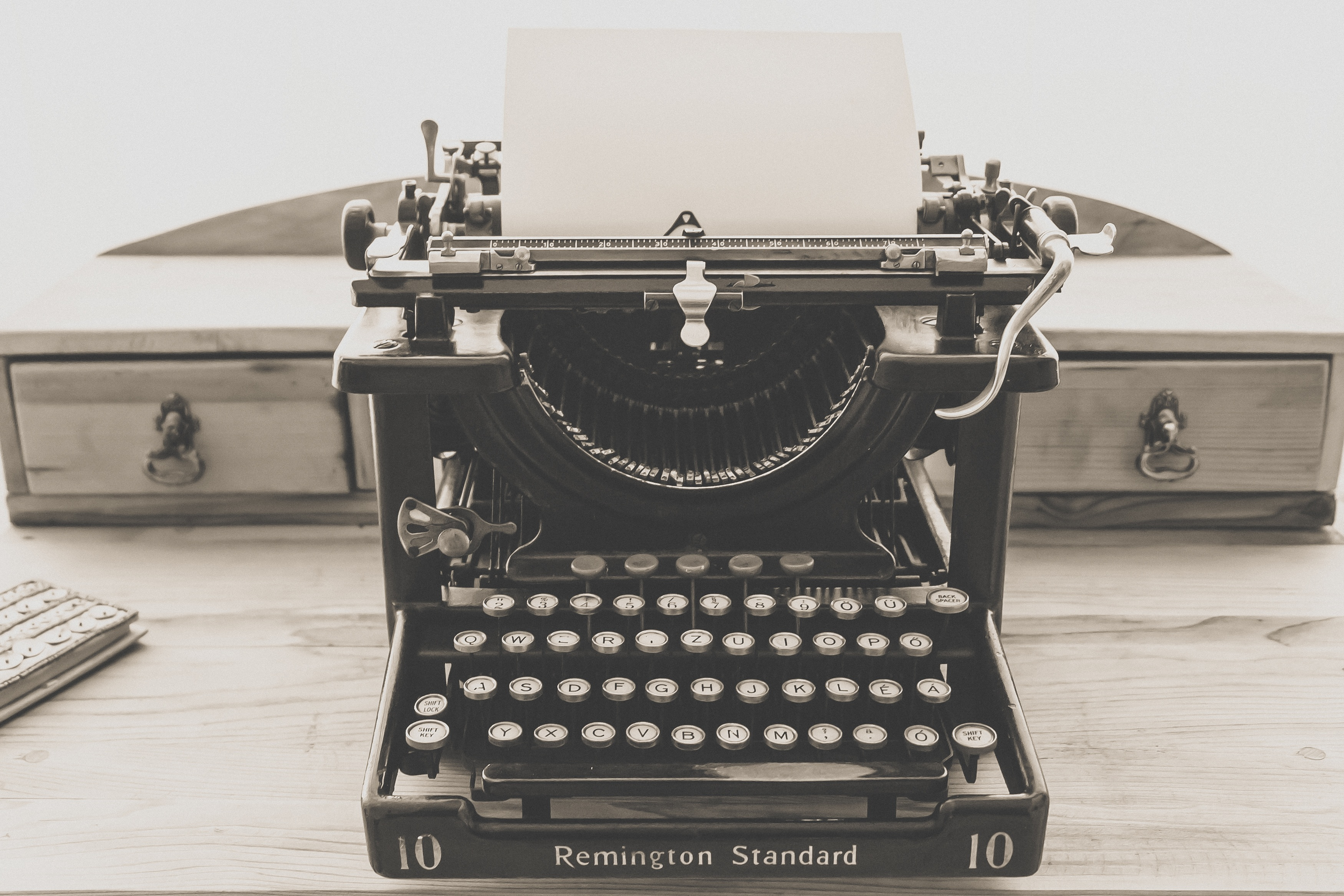 A black-and-white image of a Remington Standard typewriter on a wooden desk. In the typewriter is a blank page of paper.