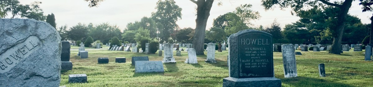 """A photograph of a cemetery. Two stones in the foreground read """"HOWELL."""" Old small stones lay behind these. The sky is pale to the point of being white, and teh grass is very green."""