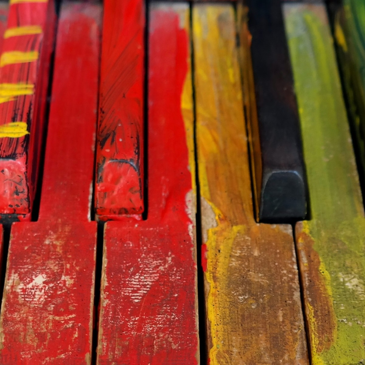 A close-up of piano keys besmeared with all colors of paint.