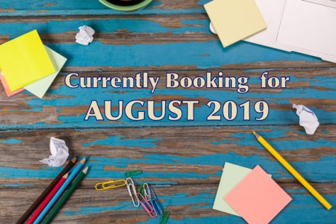 Notes on a desk with text reading: Currently Booking for August 2019
