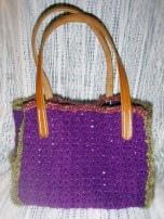 Square purse with outside pockets, leather bottom, and leather straps.