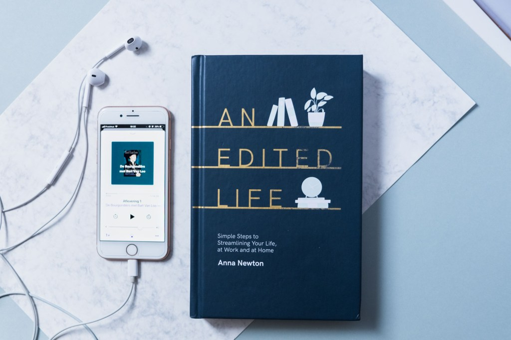 flatlay of iPhone with podcast and lifestyle book