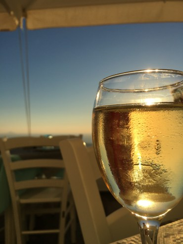 Enjoying a glass of wine and the sunset...they like to fill up your glass in Greece!