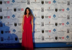 Model at luxury event in red evening gown