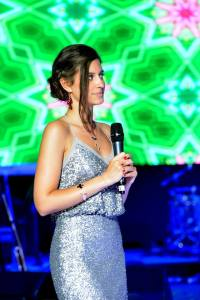 Event host with microphone in silver sequin evening dress
