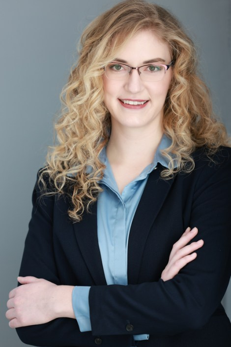 Business head shot of a young woman in a blue suit