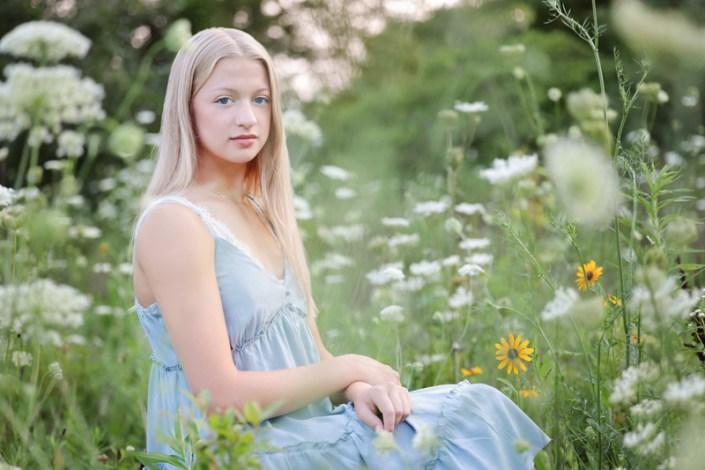 High school senior girl sitting in field of flowers