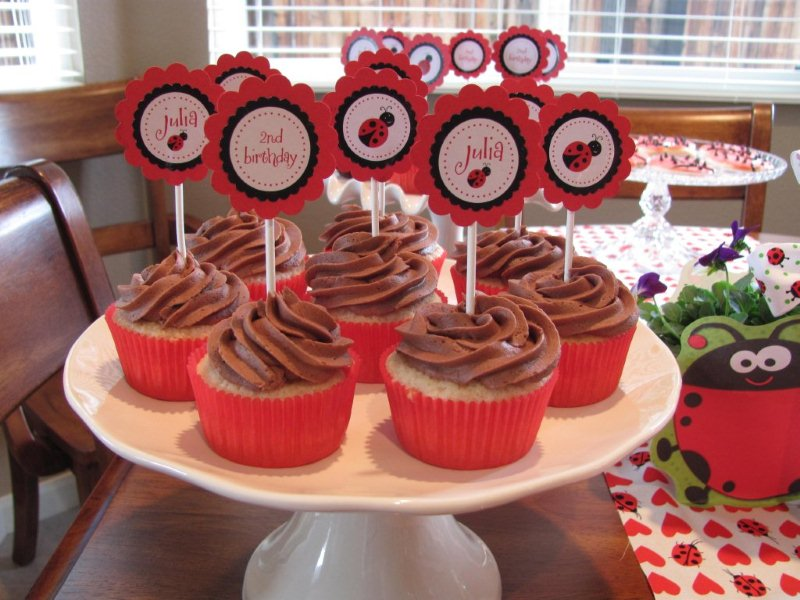 closeup of ladybug cupcakes with chocolate frosting and toppers