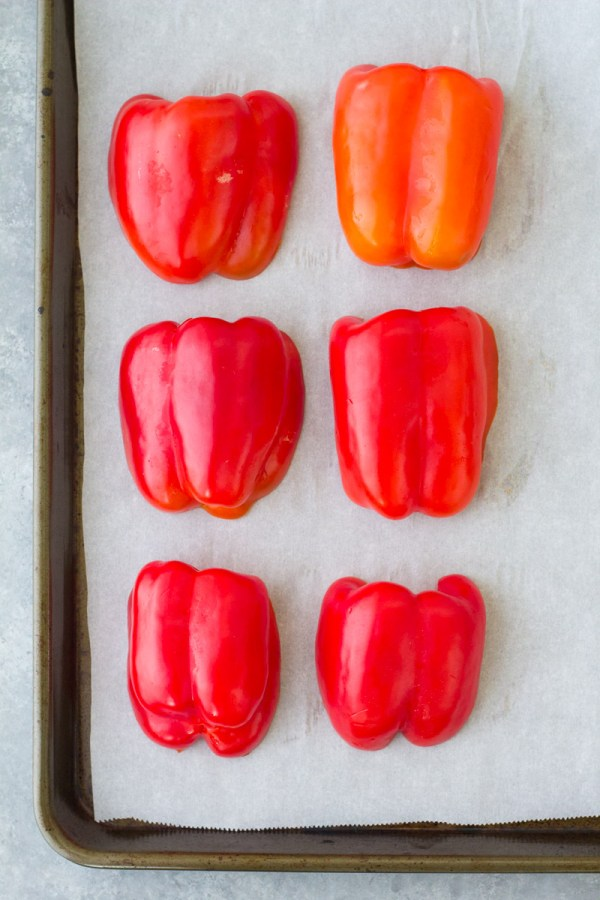 Peppers on a baking sheet, cut side down.