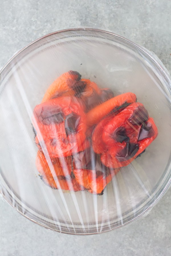 Red peppers in a bowl covered with plastic wrap.
