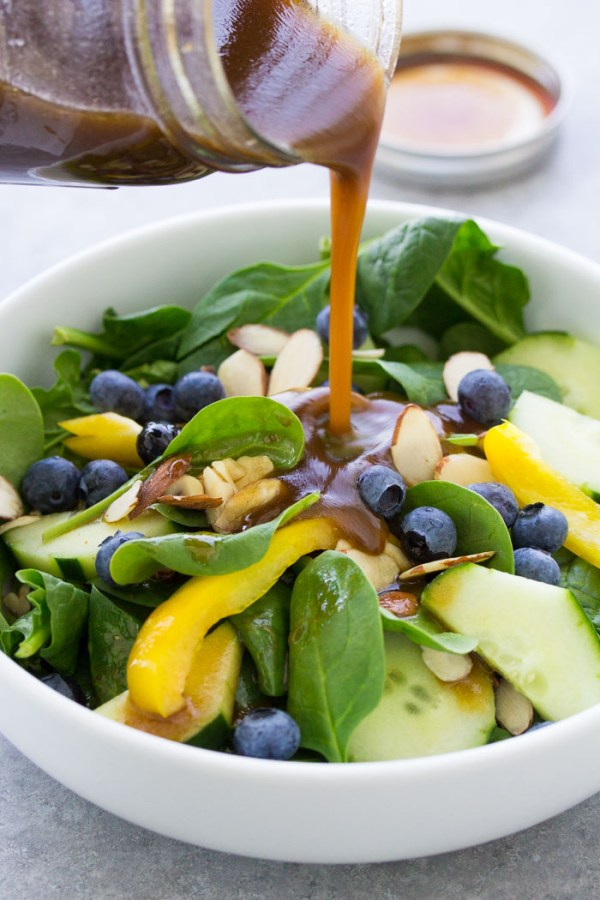 Balsamic Vinaigrette Dressing poured on a spinach salad.