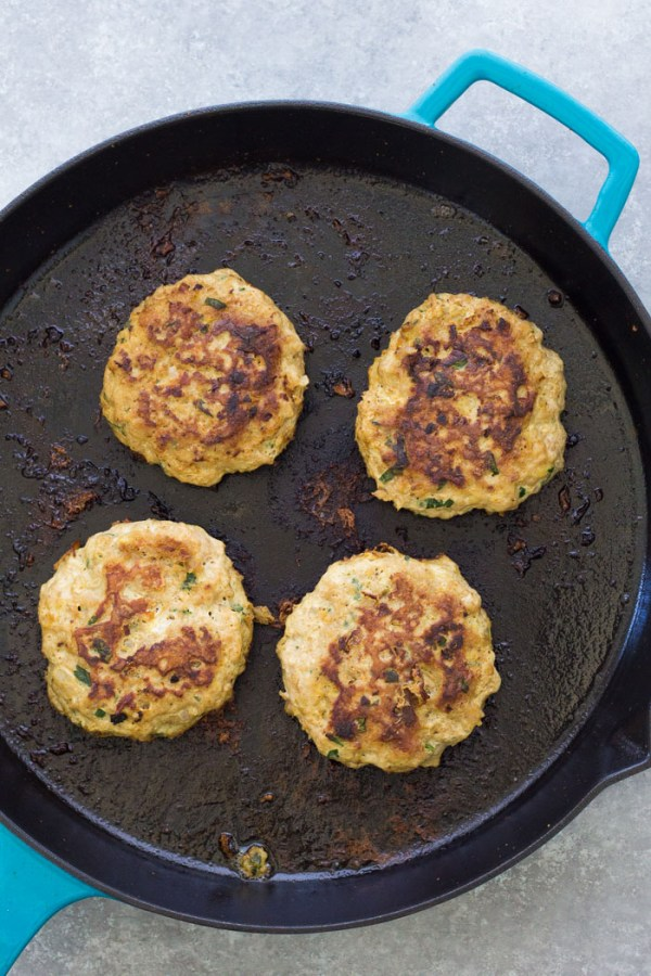 Turkey burger patties in a cast iron skillet.