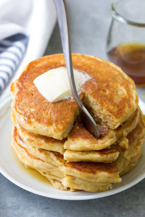 Thick, fluffy homemade buttermilk pancakes. A stack of pancakes served with butter and maple syrup.