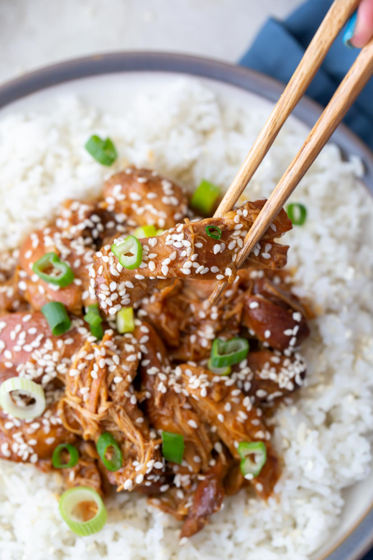 a bite of sesame chicken held with chopsticks over a plate of rice and sesame chicken