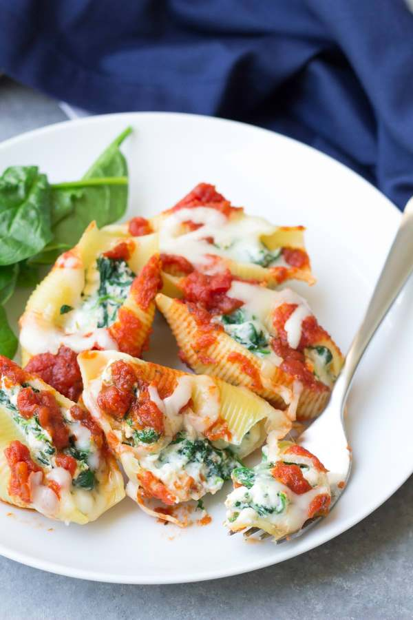 This easy Spinach and Cheese Stuffed Shells recipe is one of our favorite dinners! These pasta shells are lightened up with a secret ingredient, make ahead, and freezer friendly!