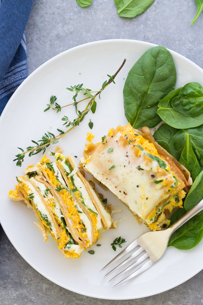 slice of butternut squash lasagna on plate cut in half with side of spinach