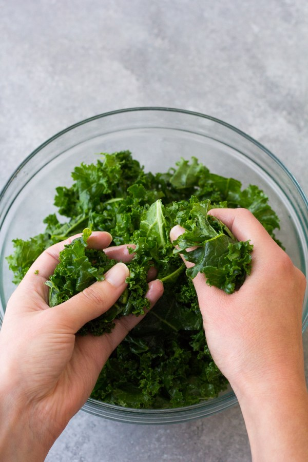 Massaging kale in a bowl with hands.