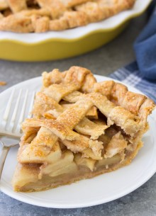 A slice of apple pie on a white plate with a fork. Whole apple pie in the background.