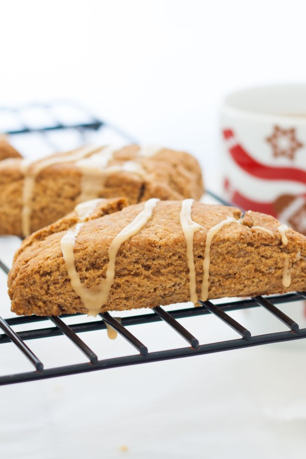 Side view of gingerbread scones with maple glaze, on a cooling rack.