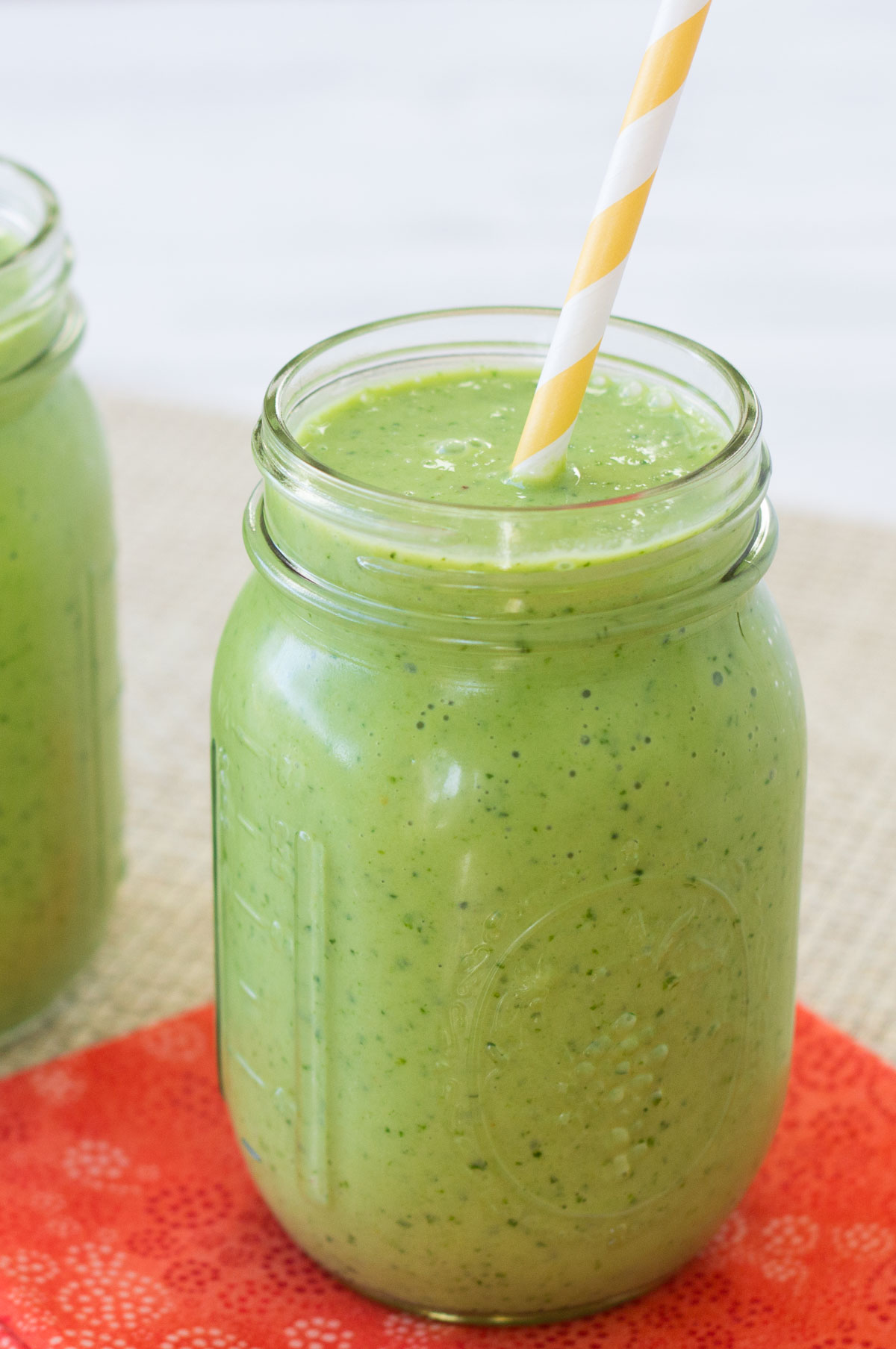 Kale smoothie in a glass with a straw.
