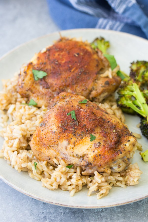 Baked chicken and rice casserole, served on a plate with roasted broccoli.