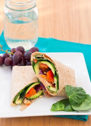 Hummus veggie wrap served with grapes.