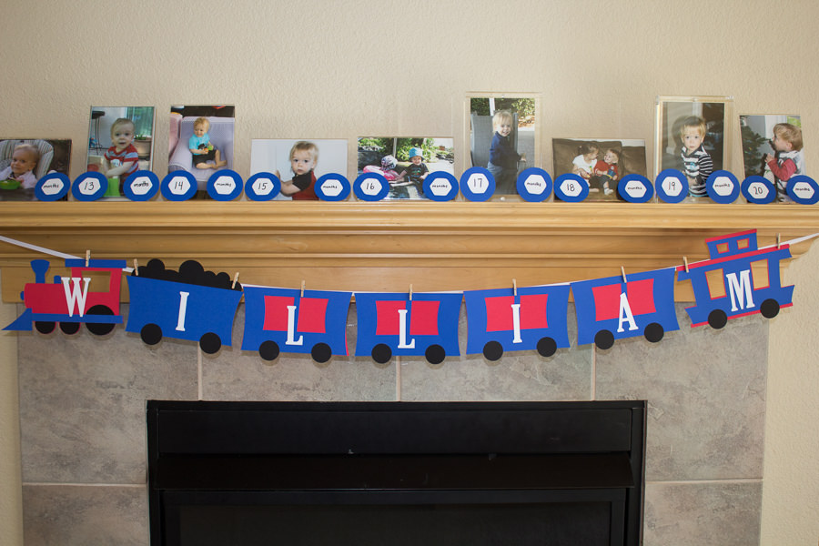 pictures on mantel at birthday party with train themed banner