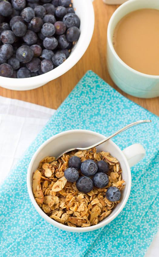 granola in white bowl topped with blueberries and adjacent dish of fresh blueberries and coffee cup