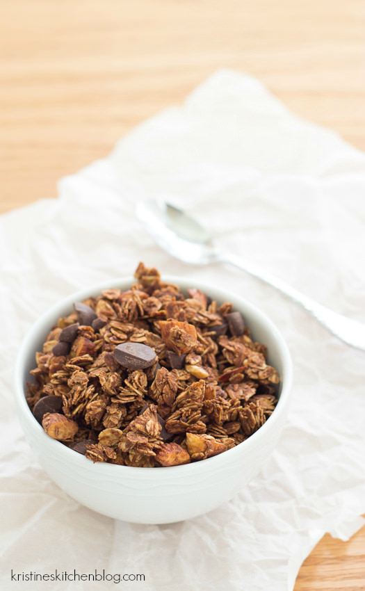 mocha granola in white bowl topped with piece of dark chocolate and almonds