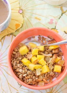 tropical granola in a bowl with milk and mango chunks
