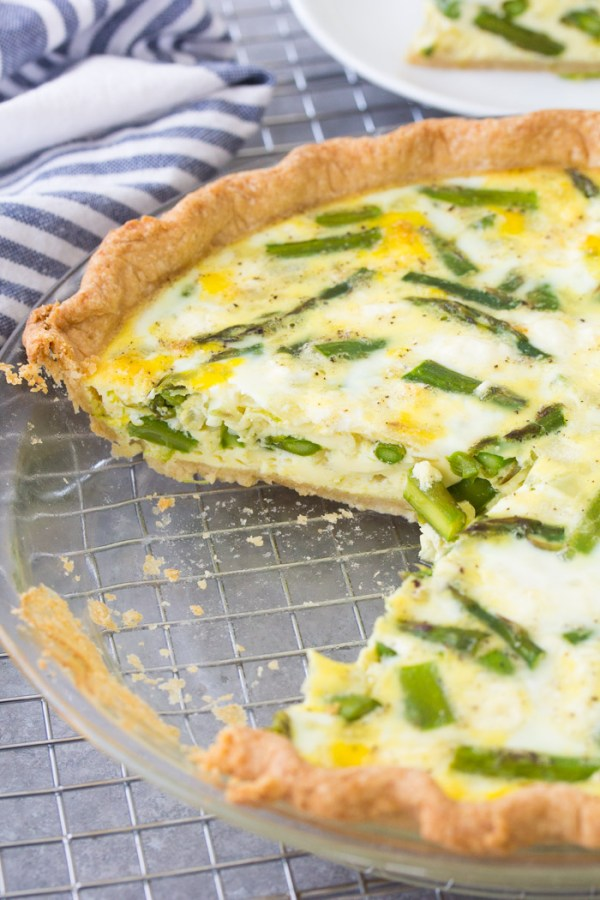 Asparagus quiche with a slice cut out of it. How to make an easy quiche.