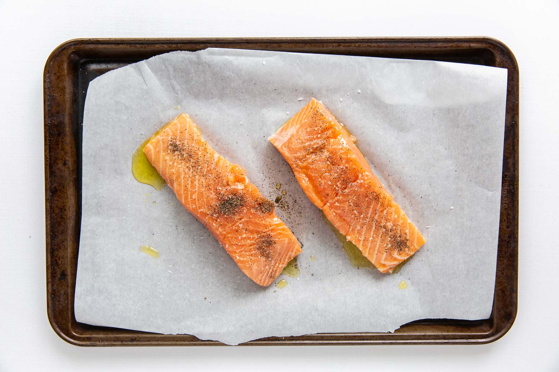 two salmon fillets with olive oil, salt and pepper on a baking sheet