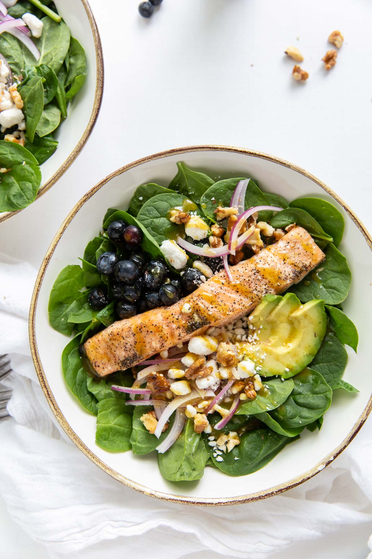 salmon salad with spinach and avocado served in a bowl and drizzled with honey mustard dressing