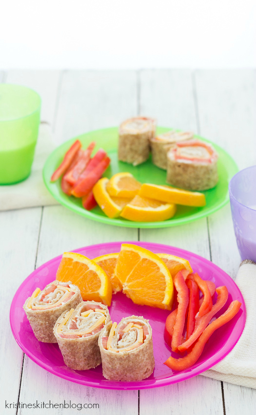 side view of kids plate with turkey and cheese pinwheels with side of fruit and vegetables