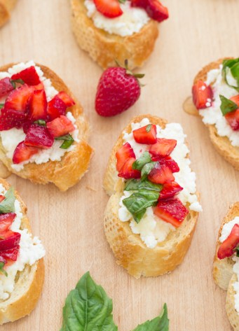 bruschetta on toasted baguette slices with ricotta, strawberries and basil
