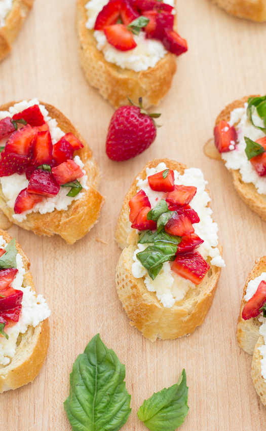 close up of bruschetta with ricotta strawberries and basil