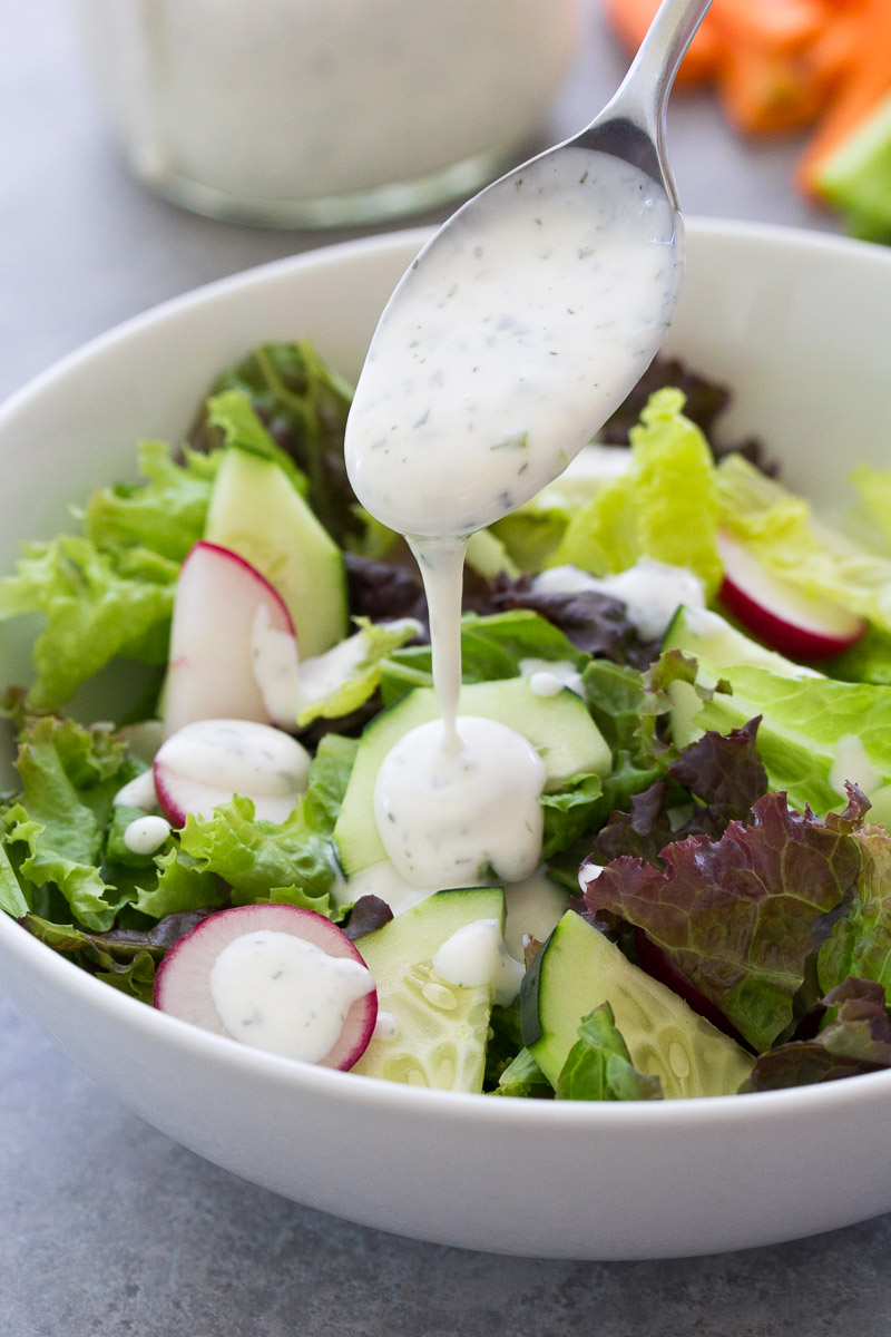 Spooning ranch dressing onto a green salad.